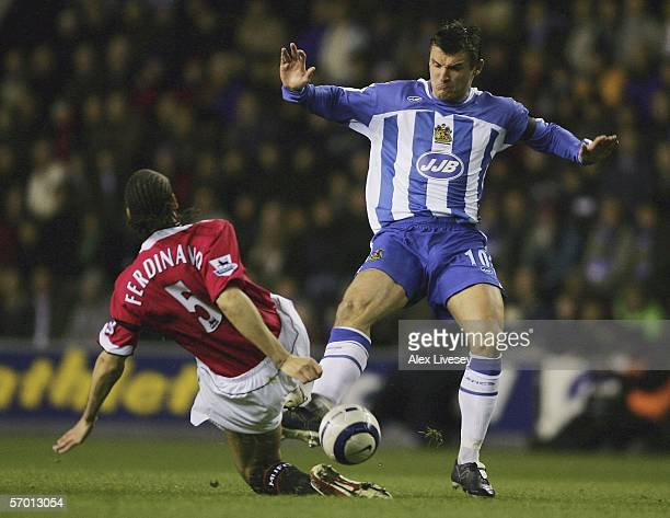 Lee McCulloch of Wigan Athletic is tackled by Rio Ferdinand of Manchester United during the Barclays Premiership match between Wigan Athletic and...