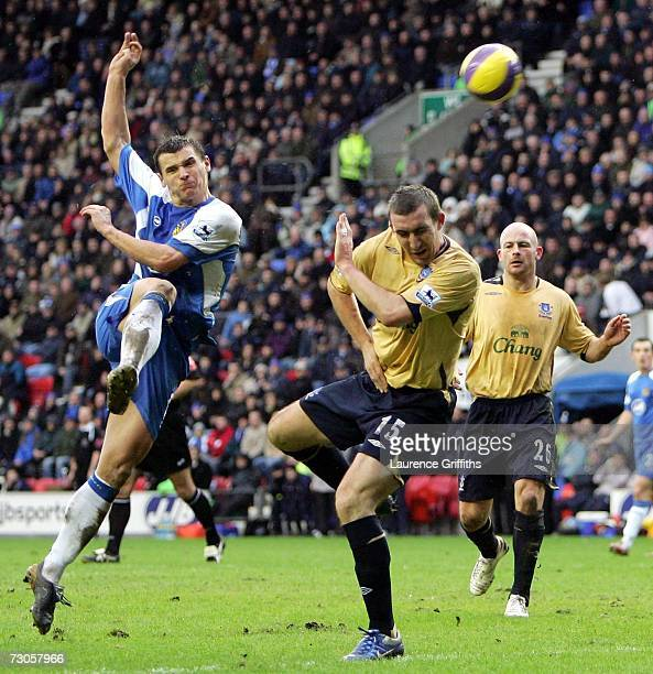 Lee McCulloch of Wigan fires in a shot under pressure from Alan Stubbs of Everton during the Barclays Premiership match between Wigan Athletic and...