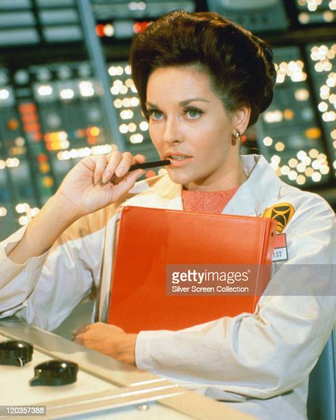 Lee Meriwether US actress sitting with a pen to her mouth while holding a clipboard dress in a white laboratory coat in a publicity portrait issued...