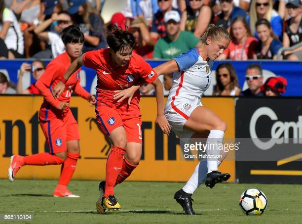 Lee Mina of Korea Republic tangles with Abby Dahlkemper of USA as they battle for the ball during their game at WakeMed Soccer Park on October 22...