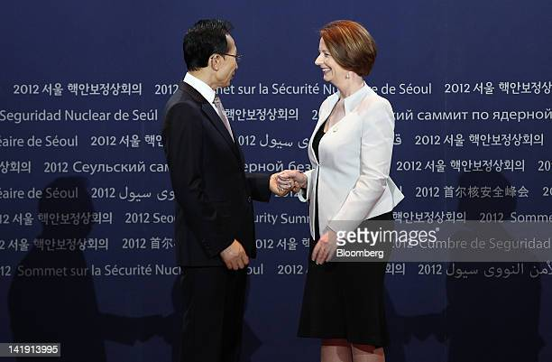 Lee Myung Bak, South Korea's president, left, shakes hands with Julia Gillard, Australia's prime minister, during a photo session before the working...