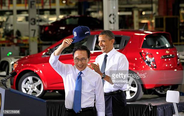 Lee Myung-bak, president of South Korea, left, tips his Detroit Tigers baseball cap to the audience as he arrives to speak with U.S. President Barack...