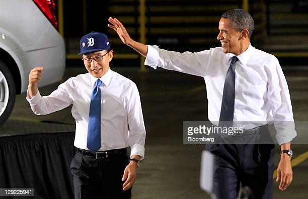 Lee Myung-bak, president of South Korea, left, wears a Detroit Tigers baseball cap as he arrives to speak with U.S. President Barack Obama at the...