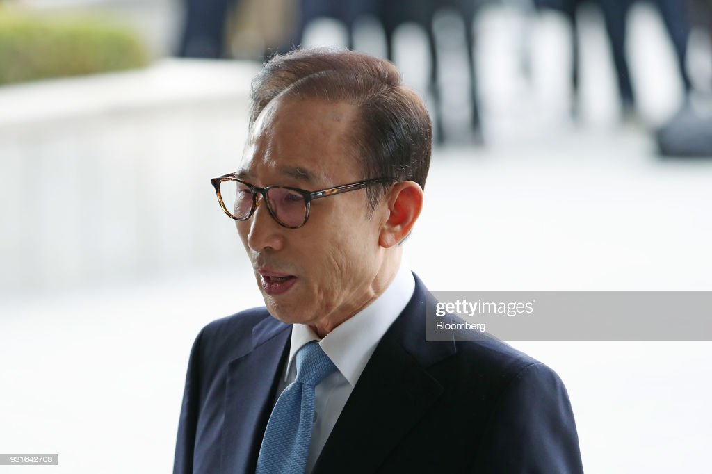 Lee Myung-bak, South Korea's former president, center, speaks as he arrives at the Seoul Central District Prosecutors Office in Seoul, South Korea, on Wednesday, March 14, 2018. Lee apologized for 'causing concern' after arriving at the prosecutors office. Photographer: SeongJoon Cho/Bloomberg via Getty Images