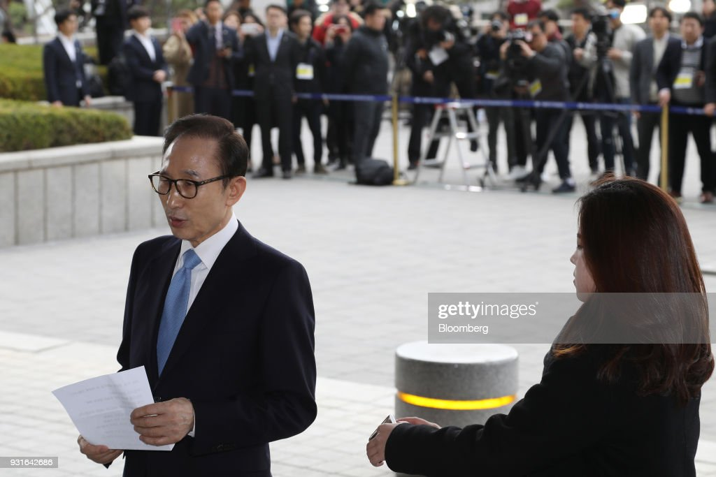 Lee Myung-bak, South Korea's former president, left, speaks as he arrives at the Seoul Central District Prosecutors Office in Seoul, South Korea, on Wednesday, March 14, 2018. Lee apologized for 'causing concern' after arriving aat the prosecutors office. Photographer: SeongJoon Cho/Bloomberg via Getty Images