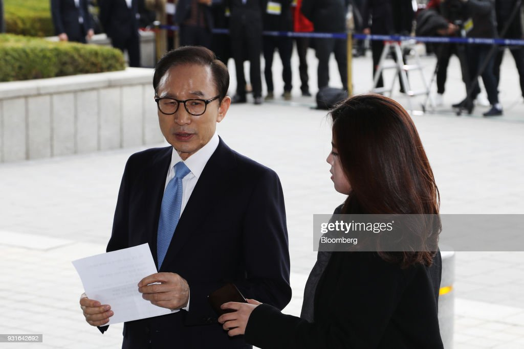 Lee Myung-bak, South Korea's former president, left, speaks as he arrives at the Seoul Central District Prosecutors Office in Seoul, South Korea, on Wednesday, March 14, 2018. Lee apologized for 'causing concern' after arriving at the prosecutors office. Photographer: SeongJoon Cho/Bloomberg via Getty Images