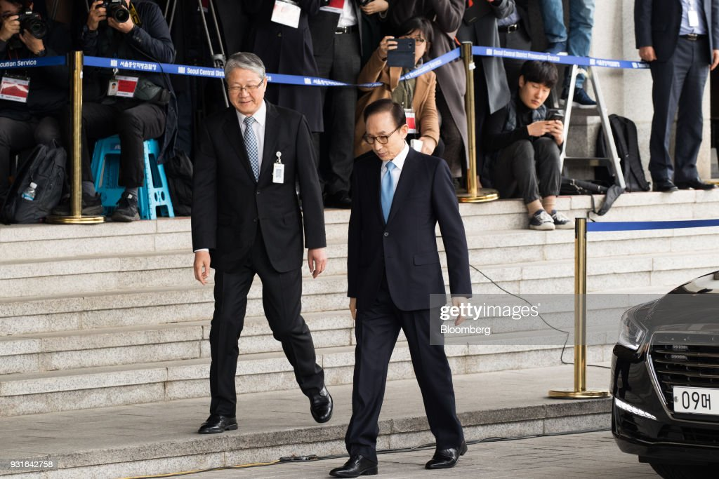 Lee Myung-bak, South Korea's former president, right, arrives at the Seoul Central District Prosecutors Office in Seoul, South Korea, on Wednesday, March 14, 2018. Lee apologized for 'causing concern' after arriving at the prosecutors office. Photographer: Lee Young-ho/Pool via Bloomberg