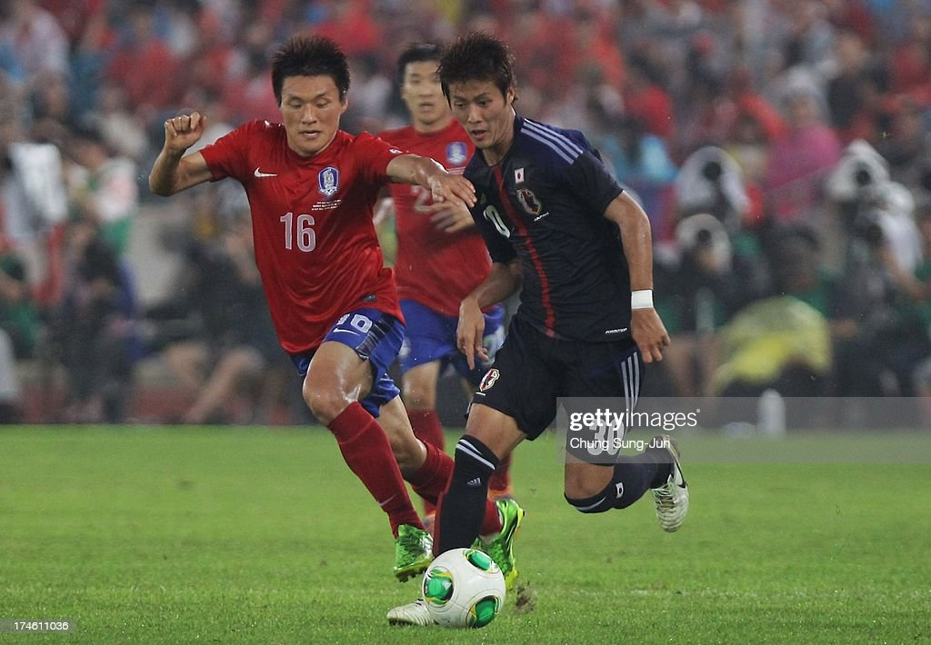 Lee Myung-Joo of South Korea competes for the ball with Yoichiro Kakitani (R) of Japan during the EAFF East Asian Cup match between Korea Republic (South Korea) and Japan at Jamsil Stadium on July 28, 2013 in Seoul, South Korea.