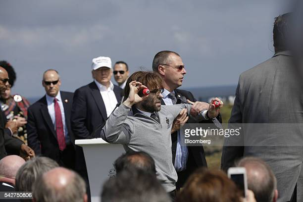 Lee Nelson, comedian, center, is restrained by security whist holding golf balls stamped with swastikas as he protests against Donald Trump,...