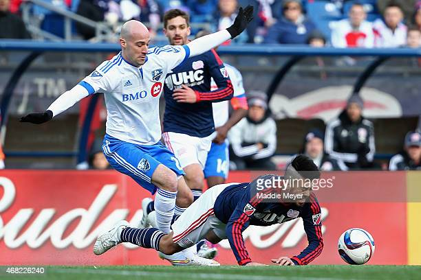 Lee Nguyen of New England Revolution is tripped by Laurent Ciman of Montreal Impact during the second half at Gillette Stadium on March 21 2015 in...