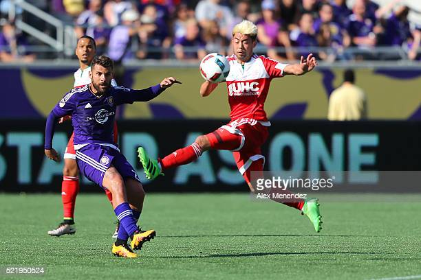 Lee Nguyen of New England Revolution jumps in front of Antonio Nocerino of Orlando City SC during a MLS soccer match at the Orlando Citrus Bowl on...