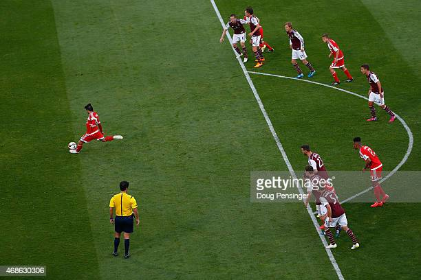 Lee Nguyen of New England Revolution strikes a penalty kick for a goal in the 54th minute to take a 20 lead against the Colorado Rapids as as referee...