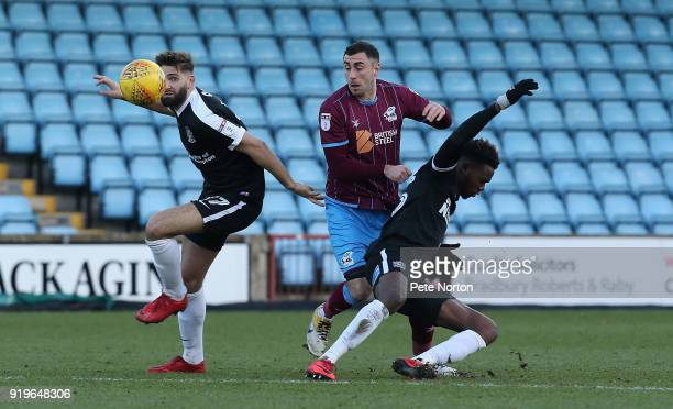 Lee Novak of Scunthorpe United contests the ball with Jordan Turnbull and Gboly Ariyibi of Northampton Town during the Sky Bet League One match...