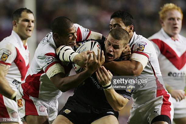 Lee Radford of Hull FC is wrapped up by Leon Pryce and Willie Talau of St Helens during the Engage Super League Grand Final between St Helens and...