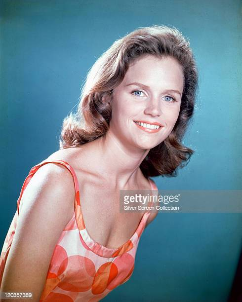 Lee Remick US actress wearing a patterned vest top in a studio portrait against a blue background circa 1965