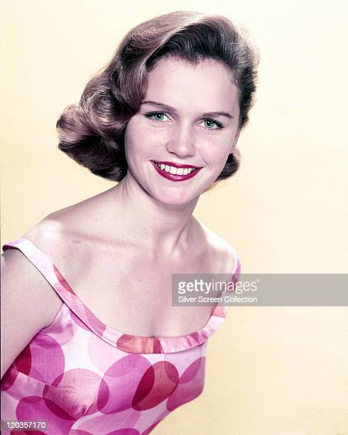 Lee Remick US actress wearing a pinkandwhite patterned print dress in a studio portrait against a white background circa 1960