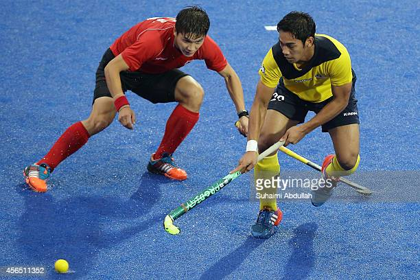 Lee Seunghoon of South Korea and Shahril Saabah of Malaysia vie for the ball during the men's bronze medal match between South Korea and Malaysia on...