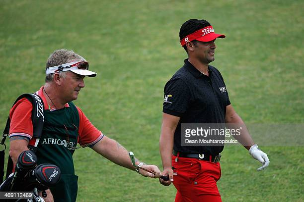 Lee Slattery of England hands his club to his caddie after he hits his second shot on the 9th hole during Day 1 of the Africa Open at East London...