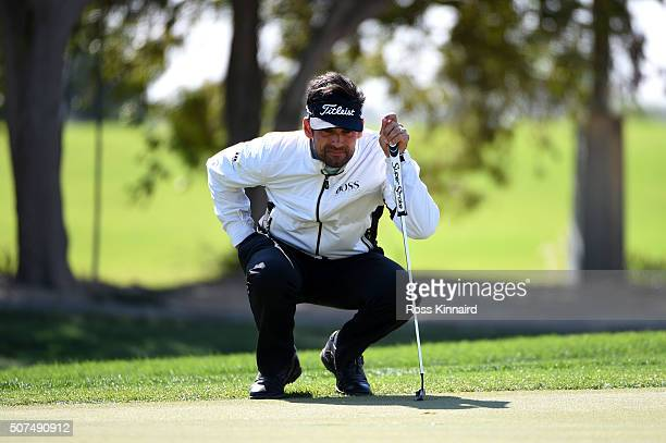 Lee Slattery of England lines up a putt on the 1st during the final round of the Commercial Bank Qatar Masters at the Doha Golf Club on January 30...