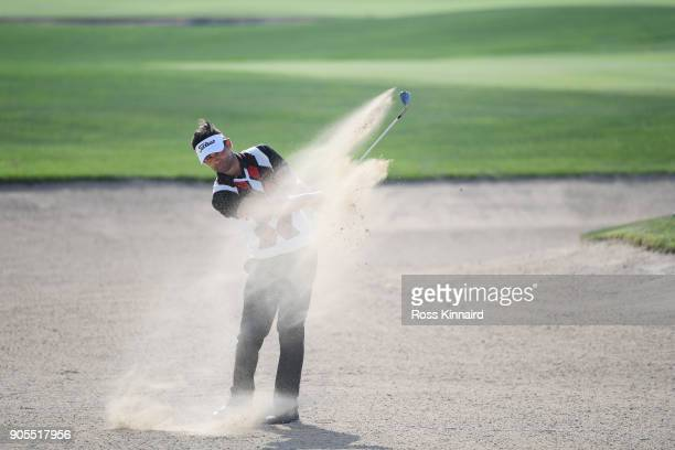 Lee Slattery of England plays a shot from a bunker on the 18th hole during practice round for the Abu Dhabi HSBC Golf Championship at Abu Dhabi Golf...