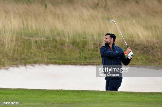 Lee Slattery of Great Britain plays his second shot from the bunker on hole twelve during match 1 of Group A during day one of the European Golf Team...