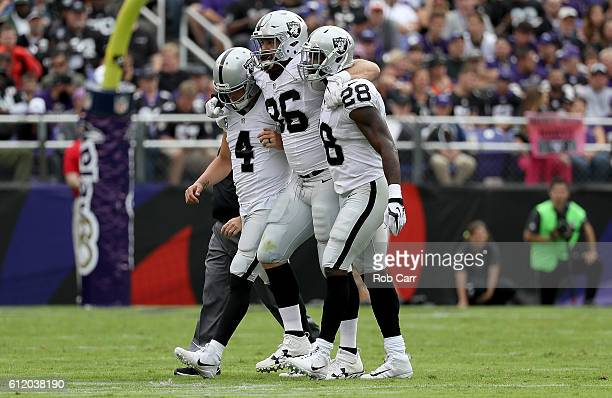 Lee Smith of the Oakland Raiders is helped off the field by Derek Carr and Latavius Murray after being injured in the second quarter against the...