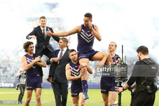 Lee Spurr of the Dockers is chaired from the field by Alex Pearce and Aaron Sandilands and Michael Johnson of the Dockers is chaired from the field...