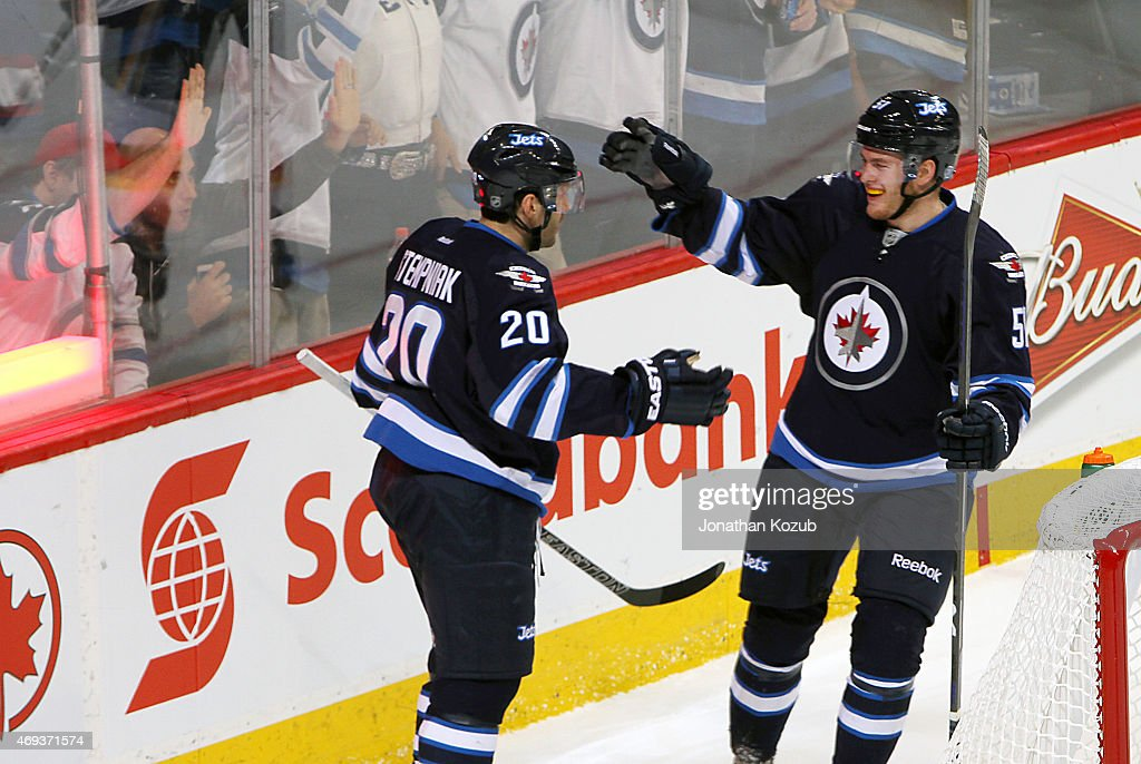 Lee Stempniak #20 and Andrew Copp #51 of the Winnipeg Jets celebrate a third period goal against the Calgary Flames on April 11, 2015 at the MTS Centre in Winnipeg, Manitoba, Canada. Copp recorded his first NHL point with an assist on Stempniak's goal.