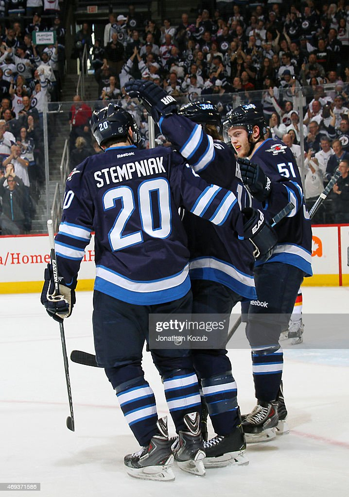 Lee Stempniak #20, Matt Halischuk #15 and Andrew Copp #51 of the Winnipeg Jets celebrate a third period goal against the Calgary Flames on April 11, 2015 at the MTS Centre in Winnipeg, Manitoba, Canada.