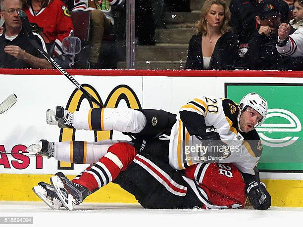 Lee Stempniak of the Boston Bruins lands on top of Marcus Kruger of the Chicago Blackhawks after a collison along the boards at the United Center on...