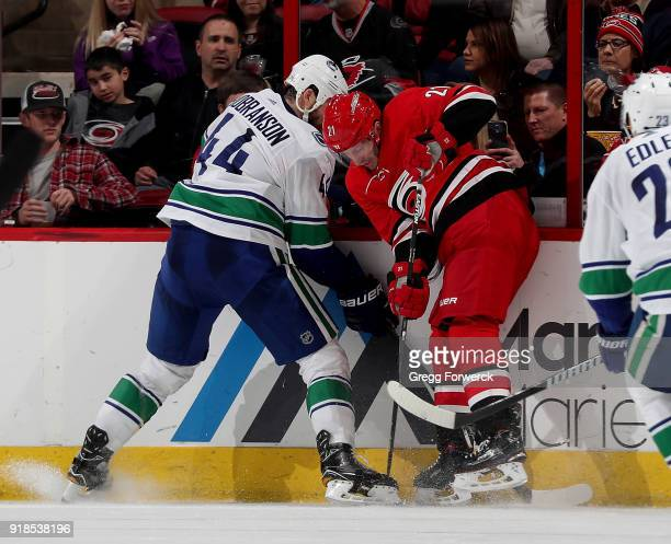 Lee Stempniak of the Carolina Hurricanes battles for a loose puck along the boards with Erik Gudbranson of the Vancouver Canucks during an NHL game...