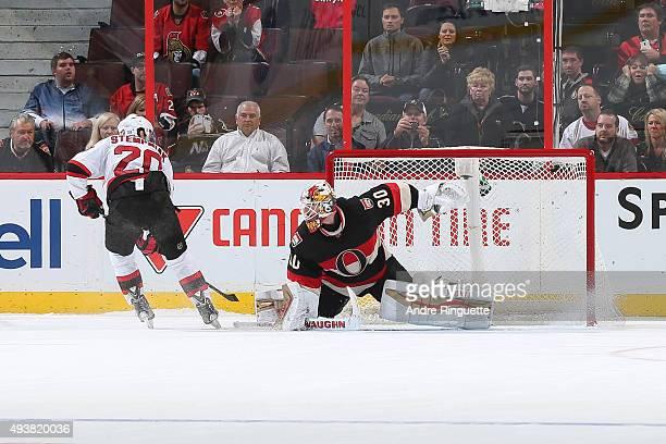 Lee Stempniak of the New Jersey Devils scores a topshelf shootout winner against Andrew Hammond of the Ottawa Senators at Canadian Tire Centre on...