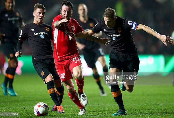 Lee Tomlin of Bristol City is challenged by Josh Tymon of Hull City and Michael Dawson of Hull City during the EFL Cup fourth round match between...
