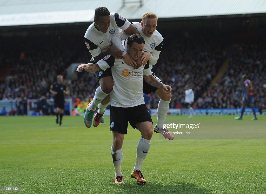 Lee Tomlin of Peterborough is jumped on by Nathaniel Mendez-Laing and Alex Pritchard as they celebrate scoring their first goal during the npower Championship match between Crystal Palace and Peterborough United at Selhurst Park on May 04, 2013 in London, England.