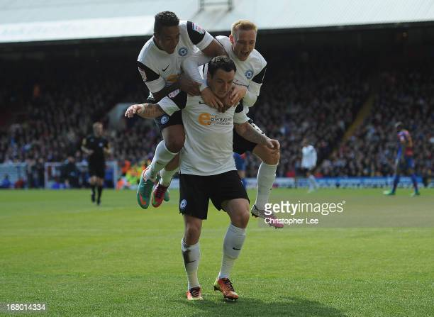 Lee Tomlin of Peterborough is jumped on by Nathaniel MendezLaing and Alex Pritchard as they celebrate scoring their first goal during the npower...