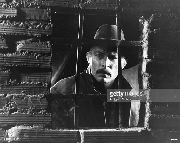 Lee Van Cleef stands behind bared window in a scene from the film 'Death Rides A Horse' 1967