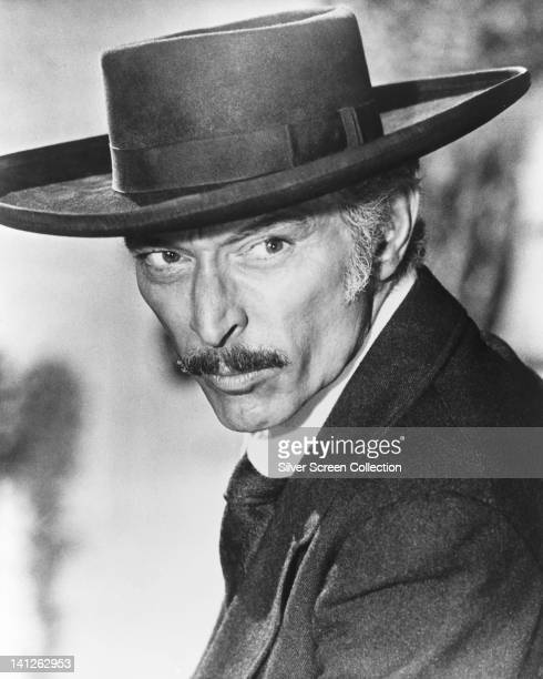 Lee Van Cleef , US actor, wearing a black wide-brimmed hat and smoking a cigar in a publicity still issued for the film, 'For a Few Dollars More',...