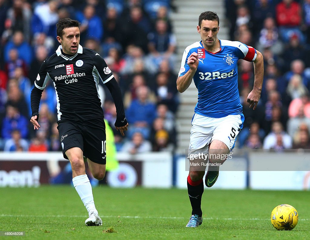 Lee Wallace of Rangers is tracked by Ryan Conroy of Queen of the South during the Scottish Championship match between Glasgow Rangers FC and Queen of the South FC at Ibrox Stadium on October 17, 2015 in Glasgow, Scotland.