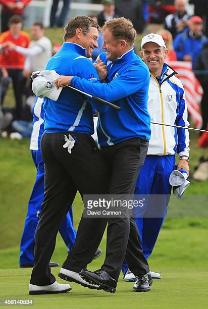 Lee Westwood and Jamie Donaldson of Europe celebrate victory watched by Europe team captain Paul McGinley during the Afternoon Foursomes of the 2014...