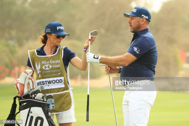 Lee Westwood of England and caddie and partner Helen Storey exchange clubs on the ninth hole during Day Four of the Abu Dhabi HSBC Golf Championship...