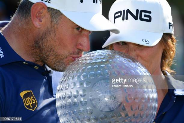 Lee Westwood of England and Caddie and partner Helen Storey kiss the trophy after Lee Westwood wins during Day Four of the Nedbank Golf Challenge at...