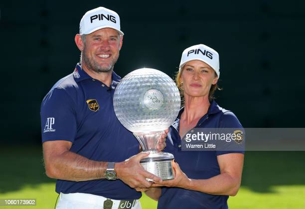 Lee Westwood of England and Caddie and partner Helen Storey lift the trophy after Lee Westwood wins during Day Four of the Nedbank Golf Challenge at...