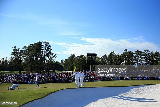 Lee Westwood of England and caddie Billy Foster line up a putt as Danny Willett of England and caddie Jonathan Smart look on on the 18th green during...