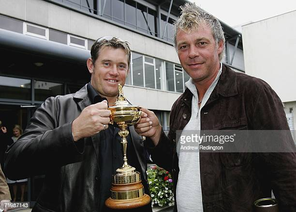 Lee Westwood of England and Darren Clarke of Northern Ireland pose with the Ryder Cup trophy as some of the victorious European Ryder Cup team gather...