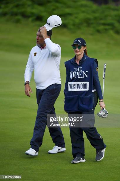 Lee Westwood of England and Helen Storey walk on the eighteenth hole during the first round of the 148th Open Championship held on the Dunluce Links...
