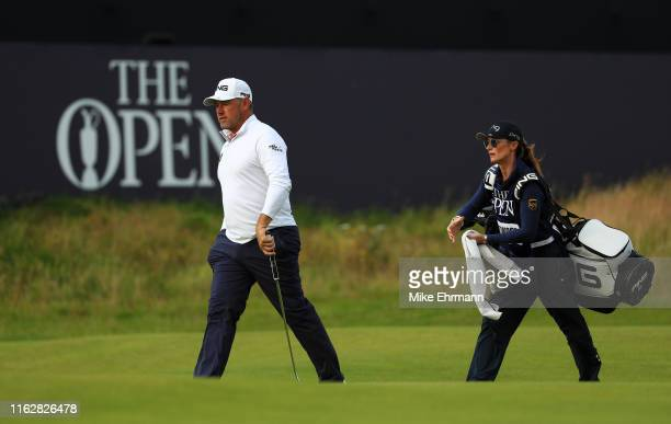 Lee Westwood of England and his caddie Helen Storey walk on the 18th green during the first round of the 148th Open Championship held on the Dunluce...
