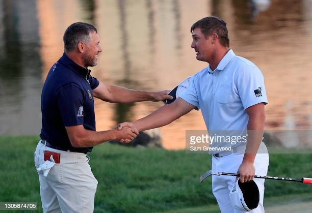 Lee Westwood of England congratulates Bryson DeChambeau of the United States on the 18th green after DeChambeau won during the final round of the...