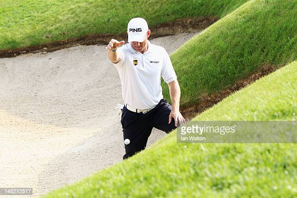 Lee Westwood of England drops the ball in to a bunker during the first round of the BMW PGA Championship on the West Course at Wentworth on May 24...