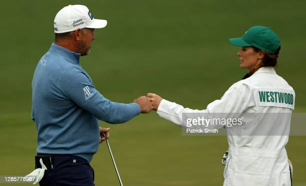 Lee Westwood of England fist bumps his caddie Helen Storey on the second green during the final round of the Masters at Augusta National Golf Club on...