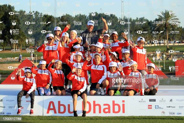 Lee Westwood of England holds the Falcon Trophy with a group of Junior Falcons after his two shot victory during the final round of the Abu Dhabi...